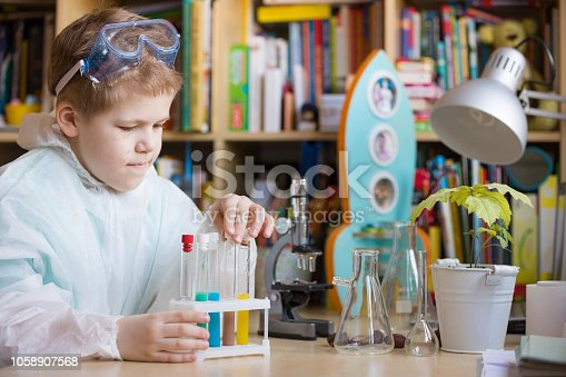 istock Cute school kid boy sitting at the table making science experiments at home. Learning activities with children at home. Doing water tests. Future profession - scientist. 1058907568