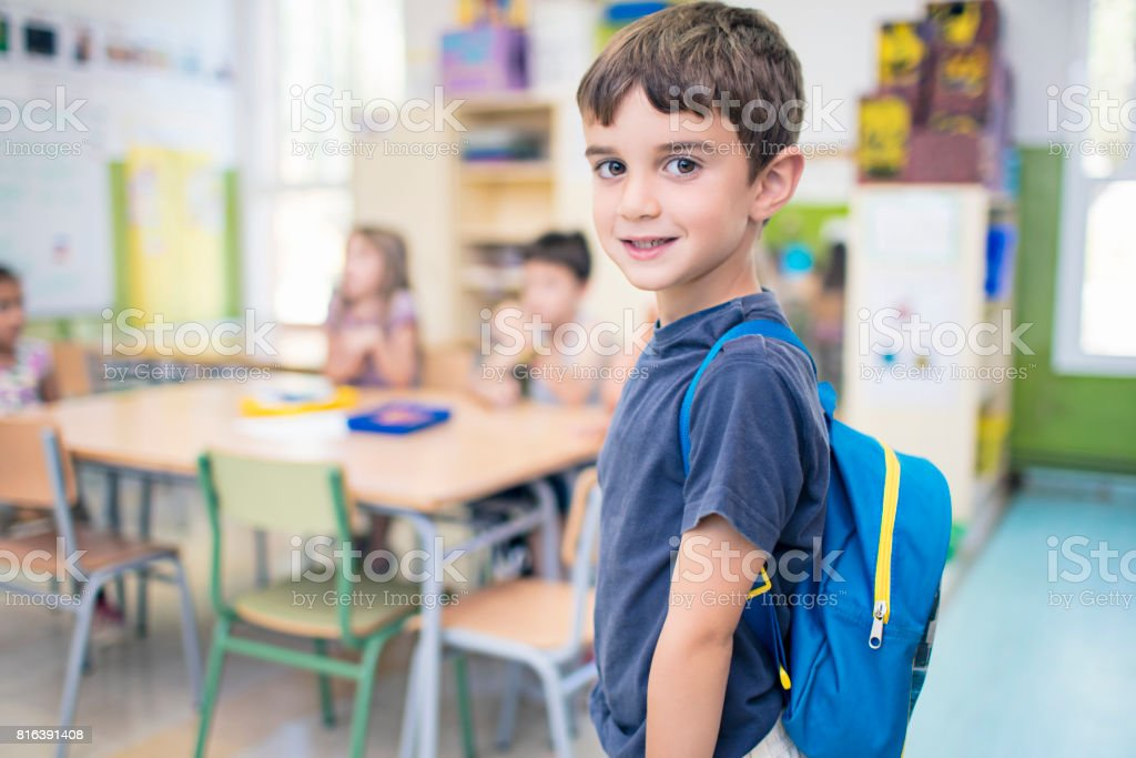 Cute schoolboy carrying backpack in classroom stock photo