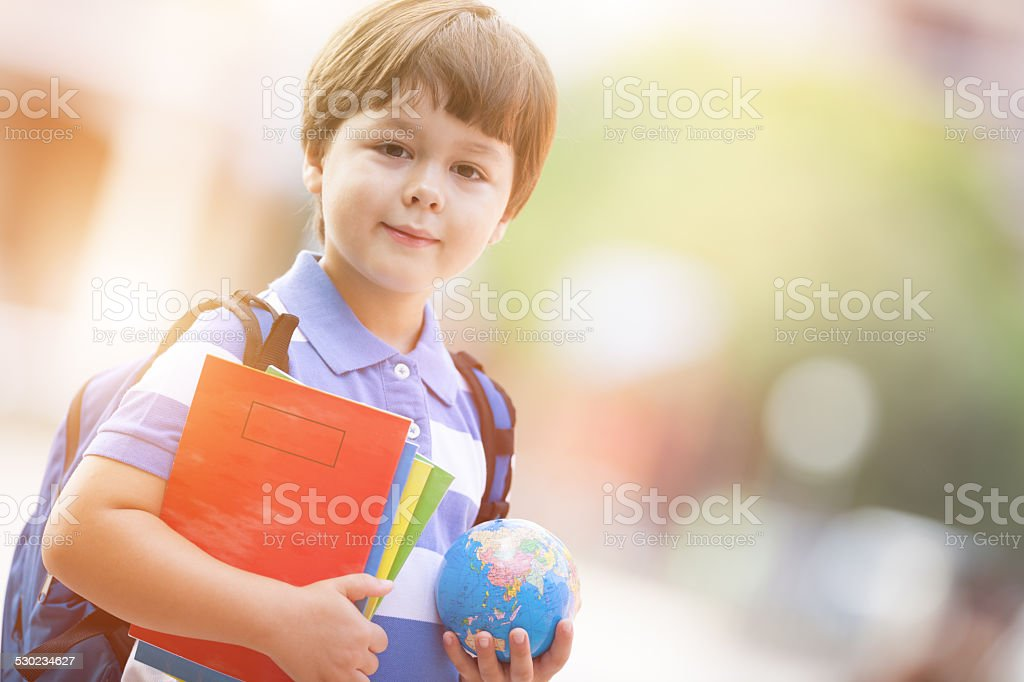 cute schoolboy in the schoolyard with school supplies stock photo