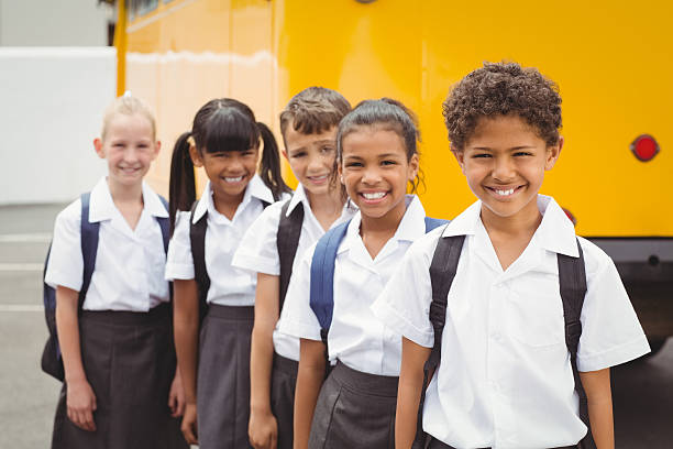 Cute schoolchildren smiling at camera by the school bus stock photo