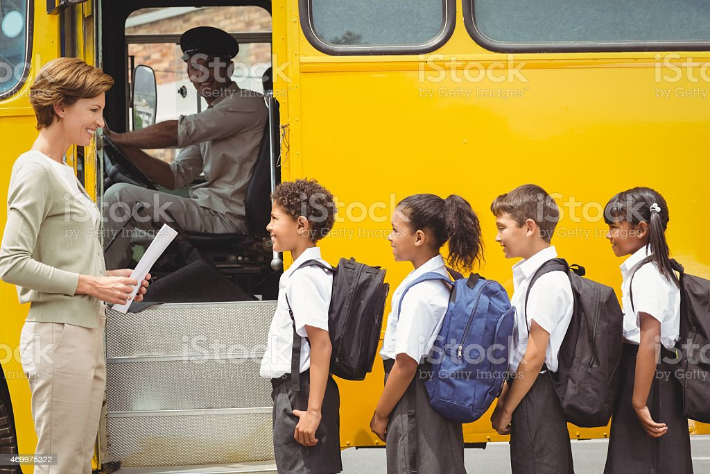 かわいい小学生の学校のバスに乗るを待って ストックフォト
