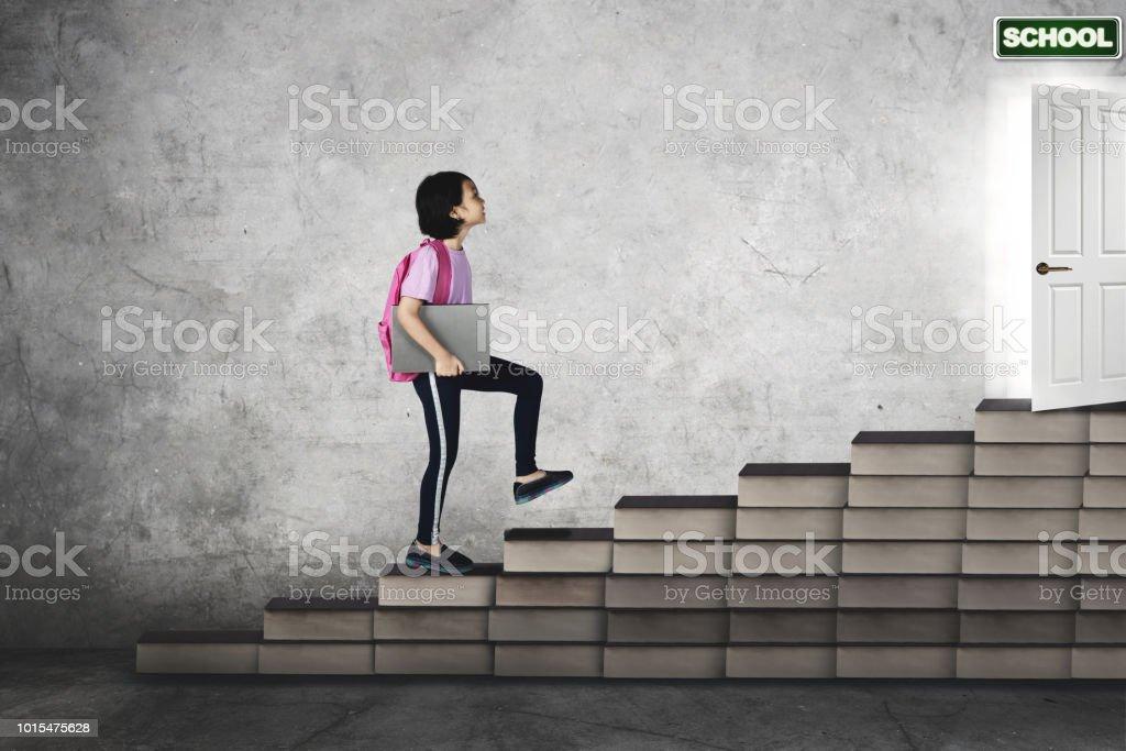 Menina bonita carrega um laptop na escadaria do livro - foto de acervo