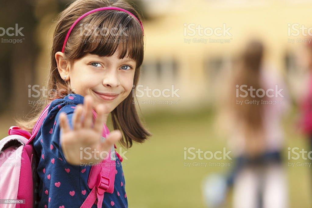 Cute schoolgirl in front of the school stock photo
