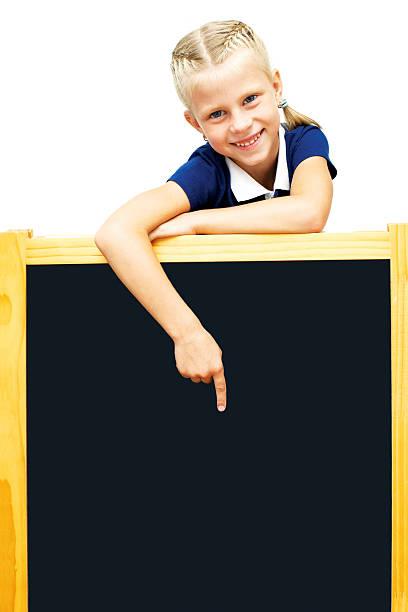 Cute schoolgirl points to a blackboard. stock photo