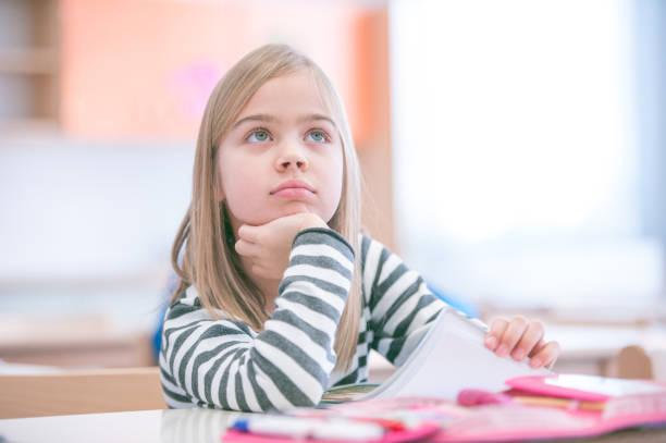 Niedliche Schulmädchen sitzen in Schule Klassenzimmer Zeichnung – Foto