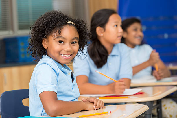cute schoolgirl smiles at the camera in classroom - uniform stock photos and pictures