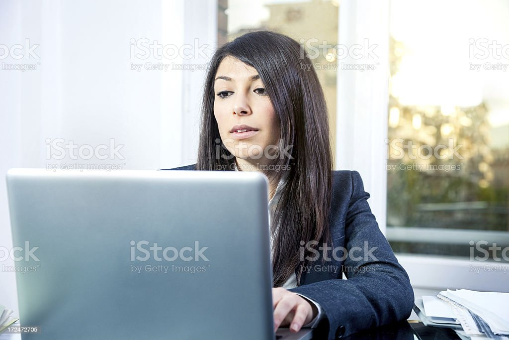Cute secretary working on laptop in office royalty-free stock photo