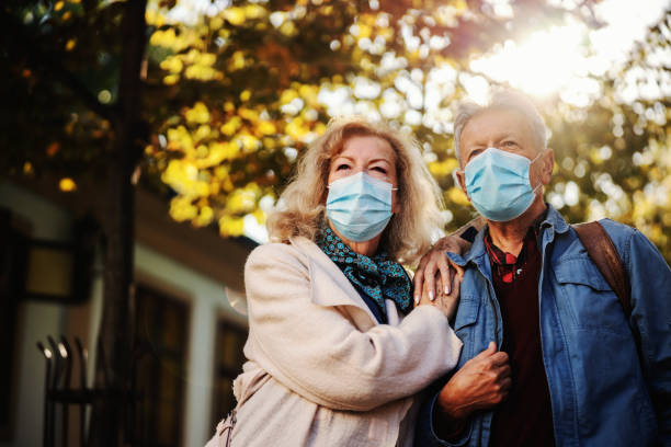 Cute senior couple with protective masks on standing in old part of the city. Woman leaning on the man. It's a sunny autumn day, perfect for walk. stock photo