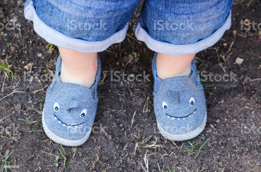 Cute shark shoes on a little boy's legs standing on dirt - view from top with bottom of his blue jean shorts showing stock photo