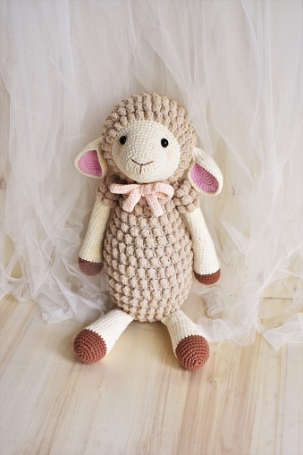 Cute sheep crochet, little animal toy for kids. Lamb crocheting and knitting background with vintage theme with chiffon and wood, home decoration with soft toys on bedroom for children, teens, preschool, nursery and elementary age. Creative handmade crochet animals background