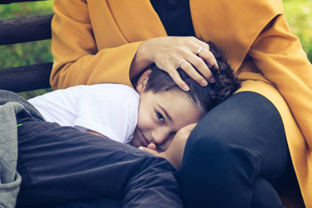 Cute shy boy hiding in mother's lap. Smiling kid relaxing on mothers lap. Shy boy feeling safe in mother's lap. sheltering stock pictures, royalty-free photos & images