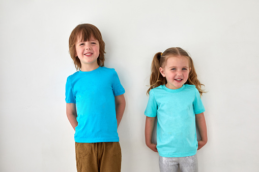 Cute siblings in blue t shirts against gray wall