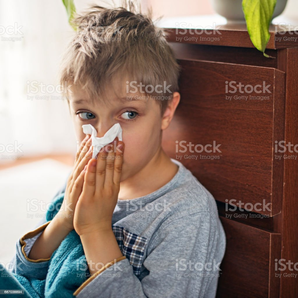 Cute sick little boy blowing nose at home stock photo