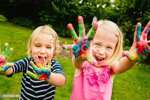 istock Cute sisters having fun with finger paint 453568449