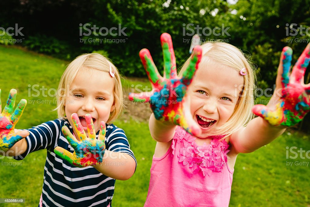 Cute sisters having fun with finger paint stock photo