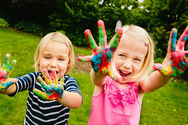 niedliche geschwister spaß mit finger streichen - fingerfarben stock-fotos und bilder