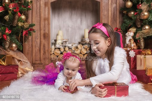 579124316 istock photo Cute sisters lying on white carpet near christmas trees 622419770