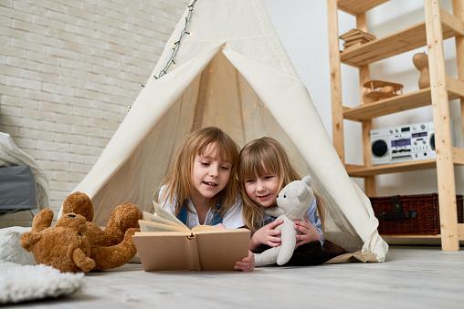 Cute sisters reading fairy tale in teepee