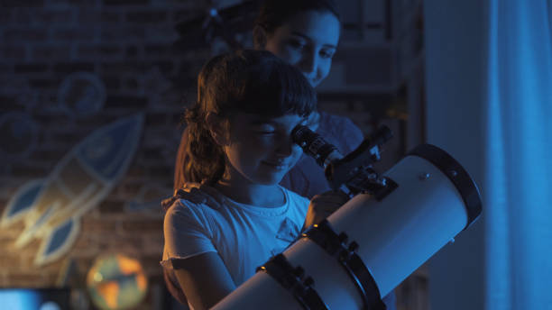 cute sisters watching the stars together at home using a telescope, family and leisure concept - astronomy stock pictures, royalty-free photos & images