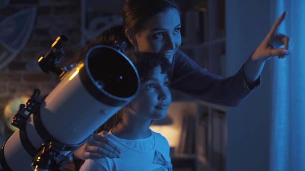 Bonitos irmãs observando as estrelas juntos em casa usando um telescópio, família e lazer conceito - foto de acervo