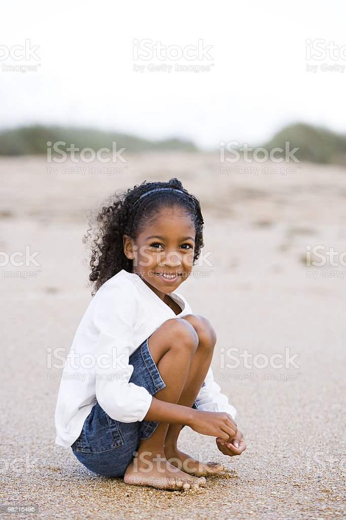 Cute six year old African-American girl on sand at beach royalty-free stock photo