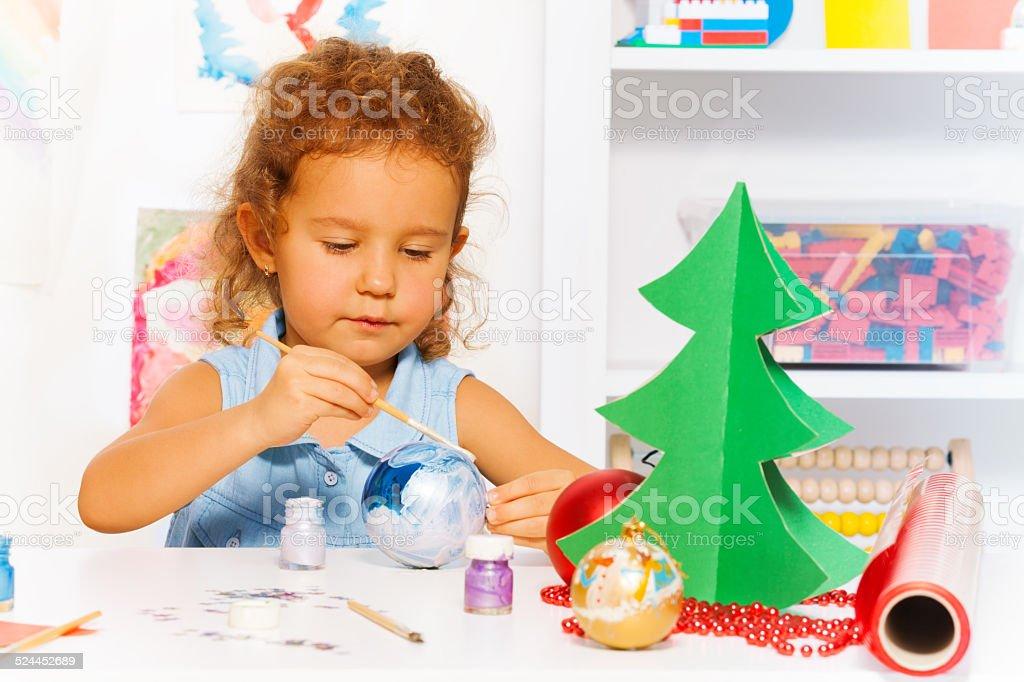 Linda chica pintura pequeñas bolas de navidad-año nuevo para el árbol - foto de stock