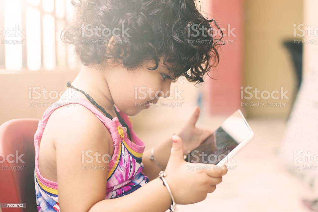 Cute small girl using a digital tablet in balcony stock photo