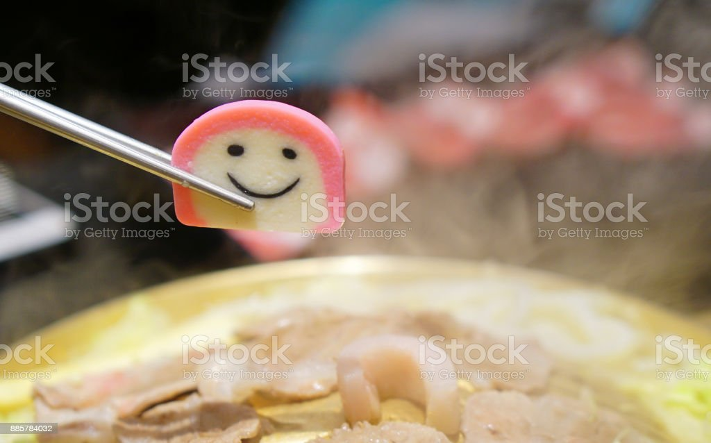 Cute small piece of food held by chopsticks over a hot barbecue pan stock photo