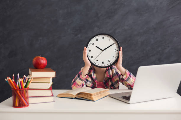 cute smart girl holding clock covering fave - girl study home laptop front imagens e fotografias de stock