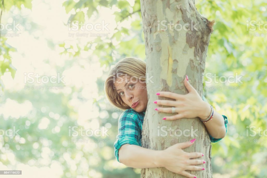 Cute smiley blonde girl touching the tree in nature. royalty-free stock photo