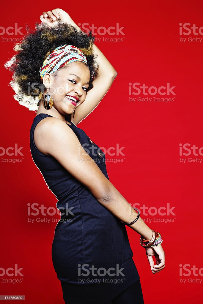 Cute, smiling, afro-haired woman laughs as she dances royalty-free stock photo