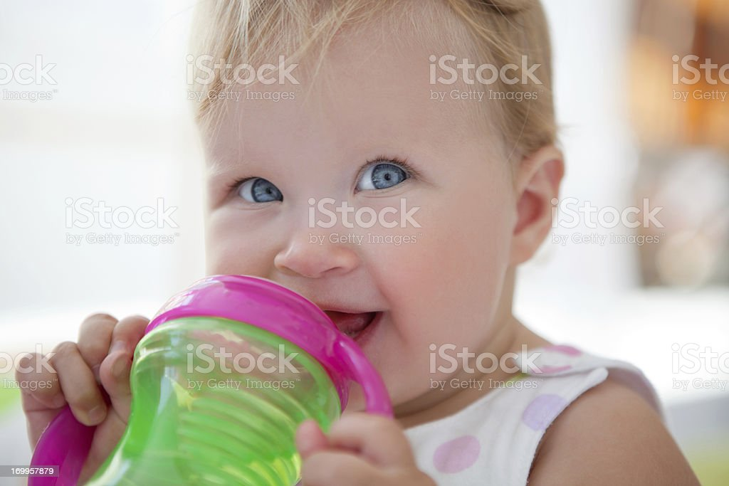 Cute smiling baby drinking water. royalty-free stock photo