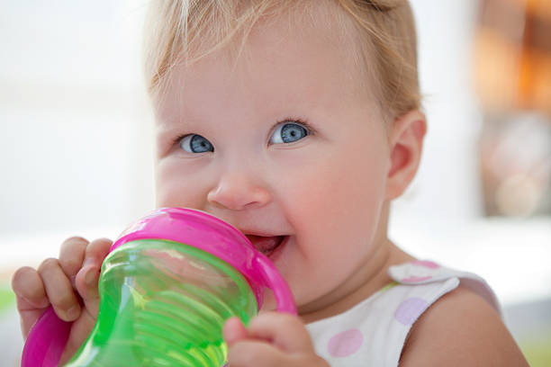 Cute smiling baby drinking water. stock photo