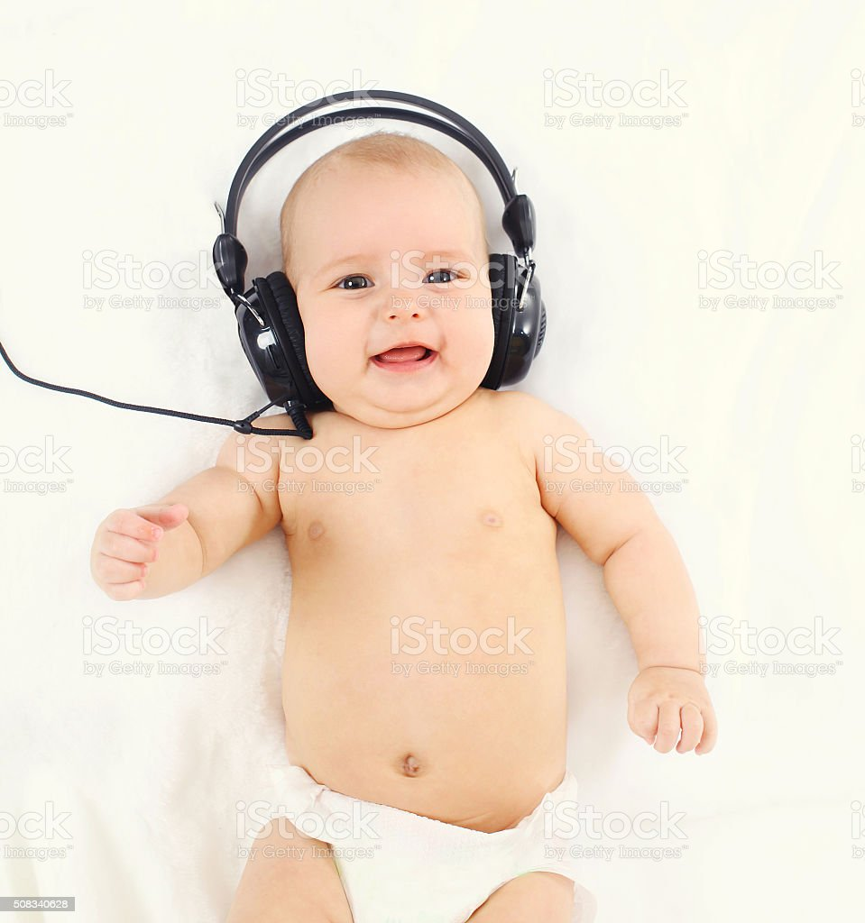 Cute smiling baby listens music in headphones lying on bed stock photo