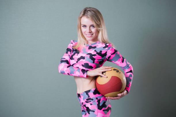 süß lächelnden blonden frau in rosa tarnung kleidung posiert mit medizinischen kugel. - rosa tarnfarbe stock-fotos und bilder