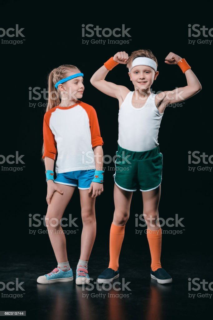 Cute smiling boy and girl in sportswear standing together isolated on black, activities for children concept Стоковые фото Стоковая фотография