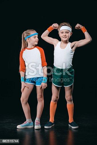 Cute Smiling Boy And Girl In Sportswear Standing Together Isolated On Black Activities For Children Concept - Fotografie stock e altre immagini di Abbigliamento sportivo