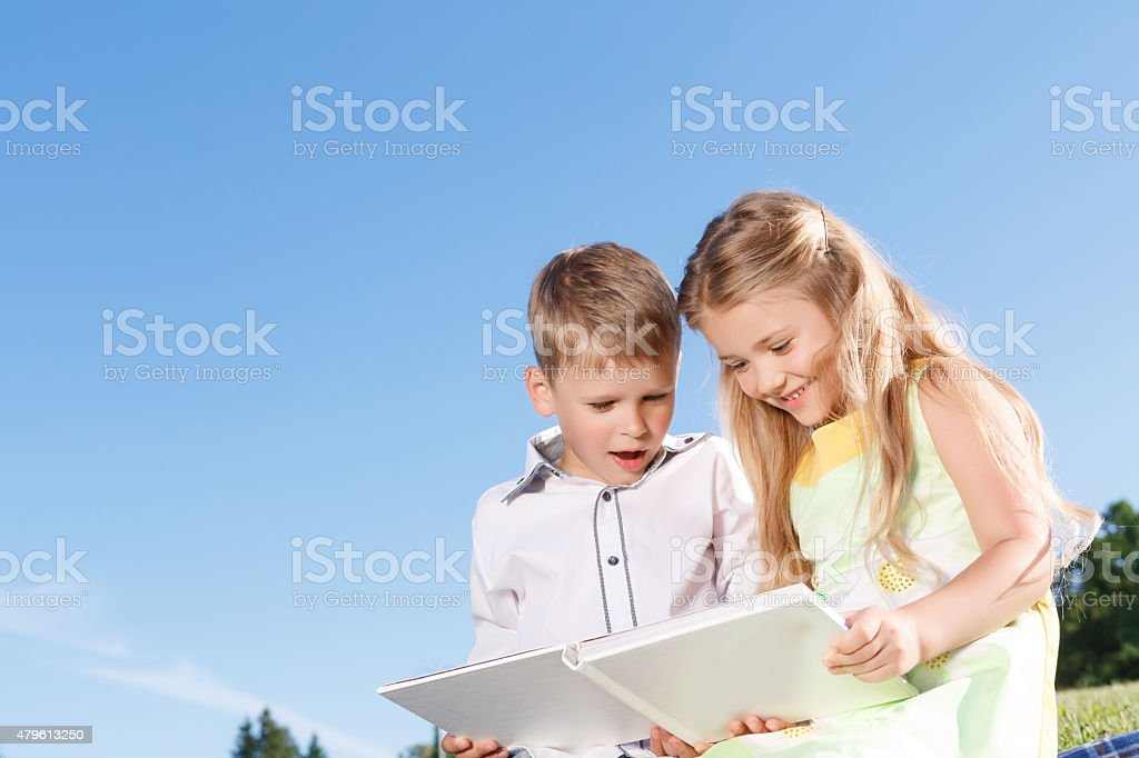Cute smiling boy and girl reading book stock photo