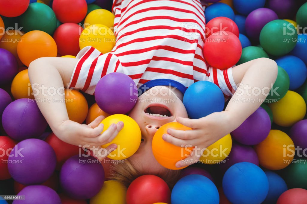Lindo niño sonriente en la piscina de la bola de esponja - foto de stock