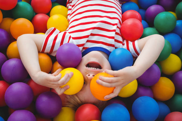 Cute smiling boy in sponge ball pool stock photo