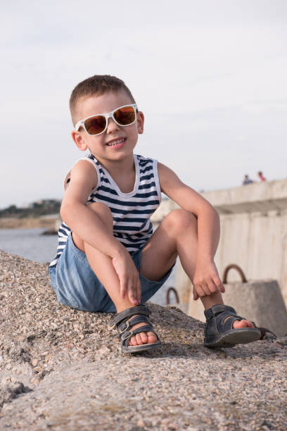 cute smiling boy in trendy sunglasses sitting on a breakwater in the port adorable smiling boy in sunglasses sitting on concrete breakwater in the port sailor suit stock pictures, royalty-free photos & images