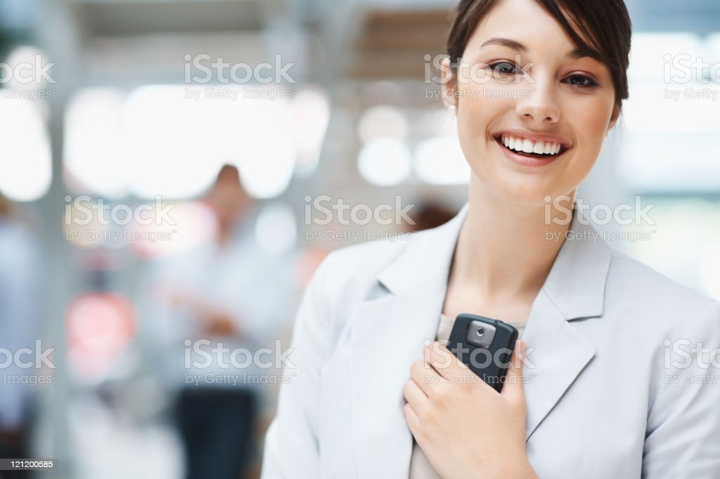 Cute smiling business female holding a cell phone Portrait of a cute smiling business female holding a cell phone on blur background Achievement Stock Photo