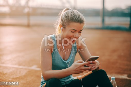 Cute smiling Caucasian blonde sporty woman sitting on the court with earphones in ears and using smart phone.