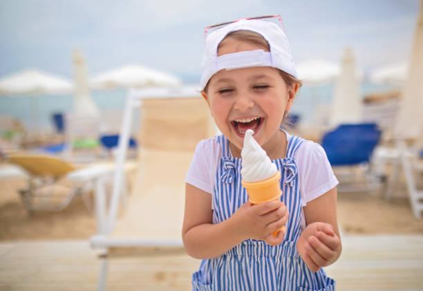Nettes lächelndes Kind isst einen Vanilleeiskegel – Foto