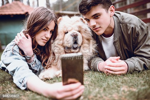 istock Cute Smiling Couple Playing with Chow Chow Dog Outdoors and Taking Selfie 948205922