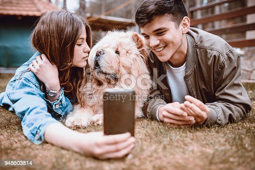 istock Cute Smiling Couple Playing with Chow Chow Dog Outdoors and Taking Selfie 948503814