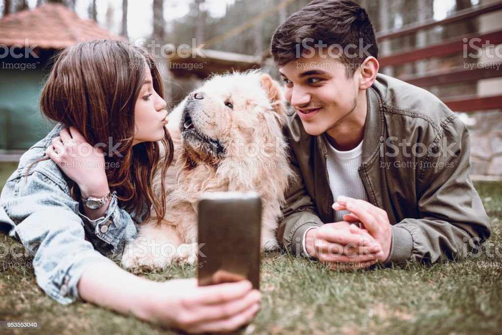 Cute Smiling Couple Playing with Chow Chow Dog Outdoors and Taking Selfie