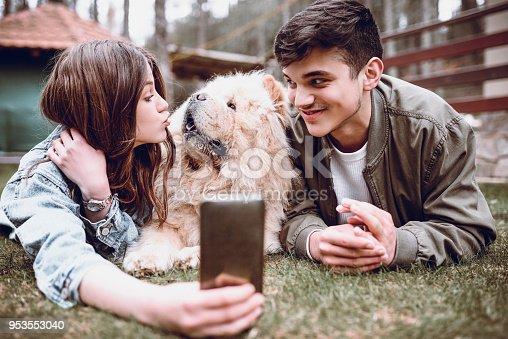 istock Cute Smiling Couple Playing with Chow Chow Dog Outdoors and Taking Selfie 953553040