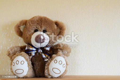 Cute smiling friendly teddy bear plush toy with bow tie sitting on wooden shelf on yellow wall background with copy space for text.