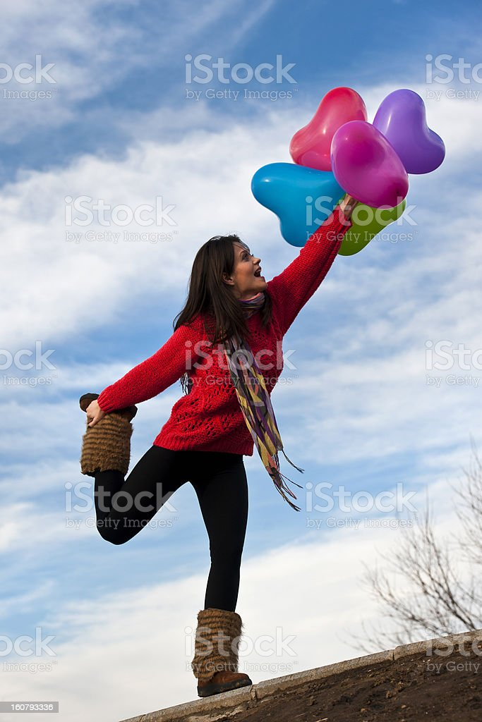 Cute smiling girl holding heart shape balloons royalty-free stock photo
